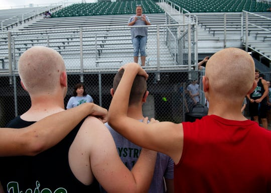 Riley Haynes, 15, center, is surrounded by his football teammates after they shaved their heads in solidarity for the sophomore linebacker/quarterback who is undergoing treatment for lymphoma at North High School's Bondurant Stadium Monday evening.