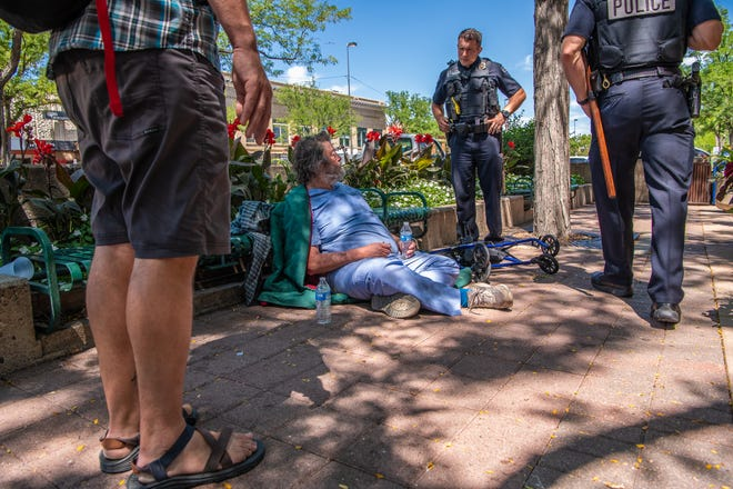 Fort Collins police officer Kyle Duncan speaks with Daniel Engilman near the corner of College Avenue and Oak Street while on foot patrol with fellow officer Nick Rogers on Friday, August 9, 2019, in Fort Collins. At left, an advocate for the homeless stands to the side, after giving Engilman bottled water. In 2019, Old Town saw a decrease in disruptive behaviors and the city's plans for a potential homeless services center came to light. The city pushed pause on a specific site and plans but are working through ideas with a board and the community.
