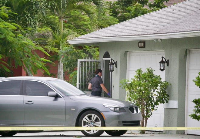 A crime scene technician enters the home where a death investigation is taking place in Cape Coral.