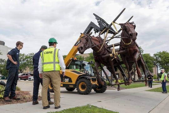 "Renco Machine Company moves the ""Logger"" statue to a trailer Tuesday, August 13, 2019, from the former Bank Mutual location on North Monroe Avenue in Green Bay, Wis. The statue was given to the Neville Museum by Associated Bank and will be displayed outside."