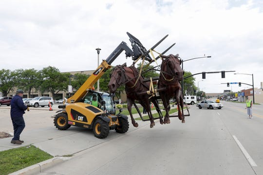 "Renco Machine Co. moves the ""Logger: statue to a trailer Tuesday, August 13, 2019, from the former Bank Mutual location on North Monroe Avenue in Green Bay, Wis. The statue was given to the Neville Museum by Associated Bank and will be displayed outside."