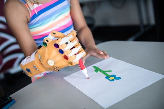 Lily Larimer, 8, signs her name on a drawing using a 3D printed hand in a laboratory at the University of South Carolina School of Medicine Greenville Thursday, August 8, 2019. Larimer, who was born with a birth defect that left her with a limb deficiency on her right hand, has been learning to use a 3D printed hand created by medical students.