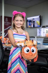 Lily Larimer, 8, with a Nemo stuffed animal in a laboratory at the University of South Carolina's Greenville campus Thursday, August 8, 2019. Larimer, who was born with a birth defect that left her with a limb deficiency on her right hand, has been learning to use a 3D printed hand created by University of South Carolina School of Medicine Greenville medical students.