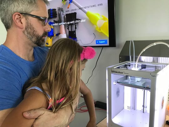Mark and Lily Larimer watch as the 3D printer prints layers for a prosthetic hand