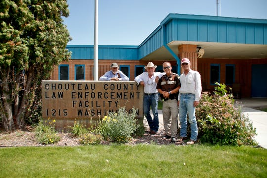 """Hollywood actor and director Ed Harris poses with his associates in front of the Chouteau County Sheriff's Office recently. Harris visited Fort Benton to seek out possible settings for his upcoming movie, """"The Ploughmen,"""" which he plans to shoot in the area in 2020. From left, set designer Waldemar Kalinowski, producer Robert Knott, Chouteau County Sheriff's Deputy Eric Visocan and director Ed Harris."""