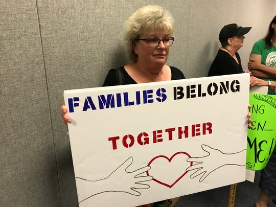 """Pam Carroll held a sign at a town hall meeting by Sen. Jon Tester in regard to children separated from their parents as they try to enter the country through the southern border. """"I know he supports us but it's still a way of getting our message out,"""" she said."""