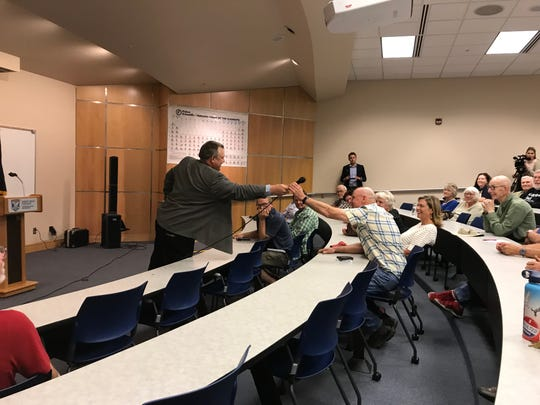 Sen. Jon Tester hands a microphone to Mark Good during a town hall meeting. Good asked Tester about the appointment of William Perry Pendley as director of the Bureau of Land Management.