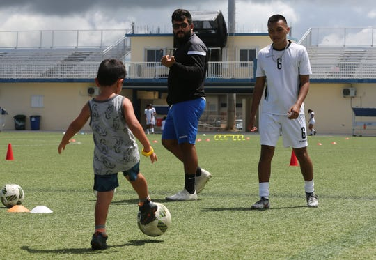 Guam U19 Men's National Training Squad's Shaun Paul Martinez assists in an activity during a soccer carnival for Harvest House kids as coach Thomas Castro observes at this year's Kåmp Tinituhon at the Guam Football Association National Training Center. The GFA Technical Department plans to expand the induction camp's offerings following the success of its inaugural edition.