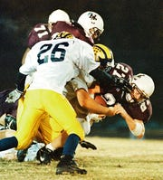 Henderson County's Eric Egan plows through Central Hardin tacklers as he rushes for a first down during a 1998 playoff game against Central Hardin.