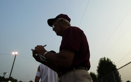 Coach George Pirtle logs his line up for the night before their game at Atkinson Park Friday night, June 21, 2002.