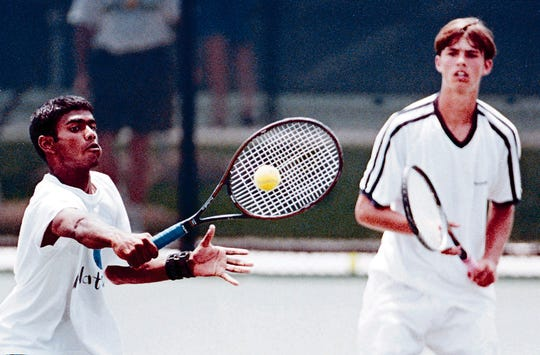 Wimal Wiljanayake, left, makes a play at the net as doubles teammate Will Graham looks on in the background during the 1998 state doubles championship match.