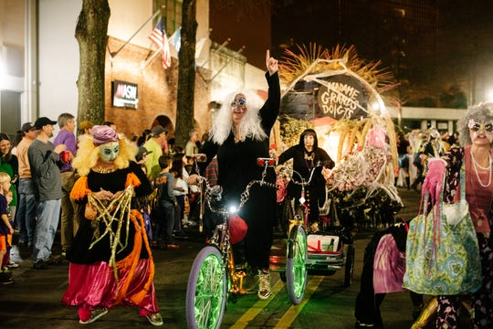 A member of sub-krewe Krewe de Cowan pedals a tricycle along Jefferson Street during the second annual Krewe de Canailles walking parade in downtown Lafayette on Friday, February 22, 2019.