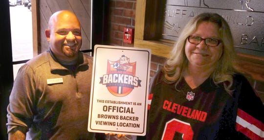 Ronda Lorenzi presents the Glass City Browns Backers sign to Buffalo Wild Wings General Manager Adam Ankrom. Game-day watch parties for all Browns games will be held there.