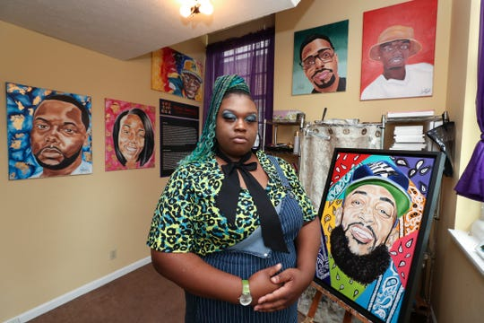 Artist Jaylin Stewart in her home studio.  Stewart paints portraits of homicide victims including L.A. rapper Nipsey Hussle on the easel next to her.