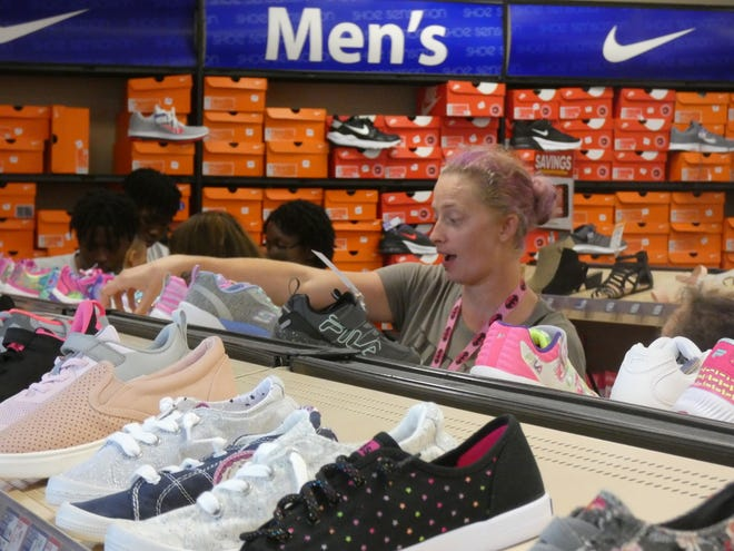 Shannon Davis shops for back-to-school shoes for her daughter Alice Davis, a 2nd grader at Heritage Elementary School, Tuesday during the first of two days the local charity Cents for Shoes is giving away kids' shoes at little or no cost to eligible families.