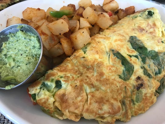 An omelet with roasted cauliflower, bell pepper and other vegetables is served with potatoes and guacamole made from edamame, or soybeans, at Orenda. The plate also comes with toast.