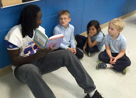 Chris Garrett, left, reads to kindergarten students in the Reading Buddy Program. A 2017 graduate of Wisconsin Lutheran High School, Garrett overcame a tough childhood and lagging academics to become an education major in college.
