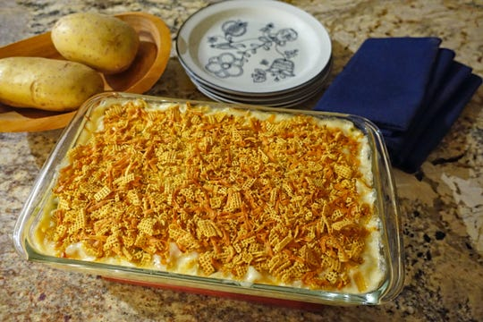 Cheesy potato casserole is topped with a mixture of crushed Corn Chex and smoked cheddar cheese before baking.