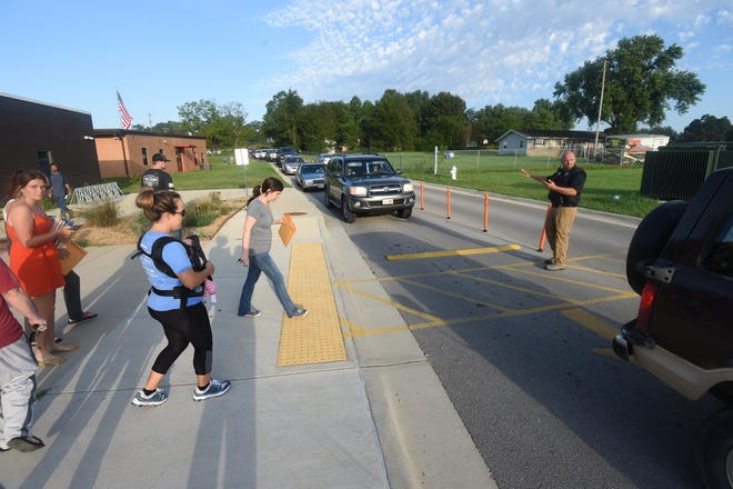 Flippin police officer Lonnie Stone directs traffic Tuesday outside Flippin Elementary School. Local law enforcement agencies are asking motorists to exercise caution as the new school year has begun.