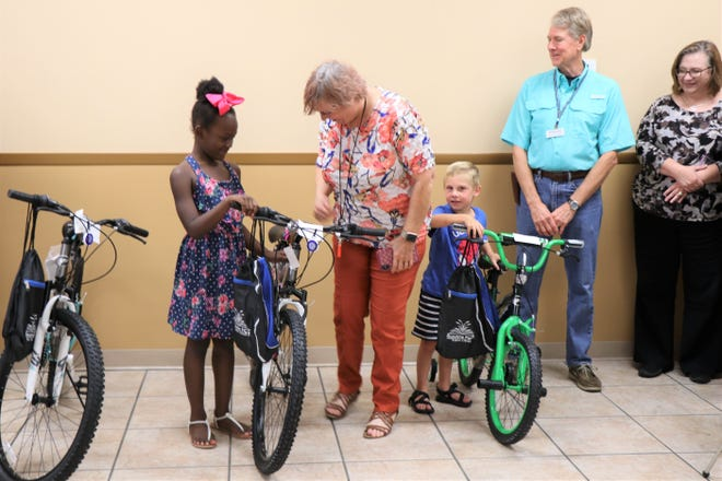 West Monroe children's assistant Judy Creekmore looks at the new bikes with Tazirea Holland and Judah Campbell.