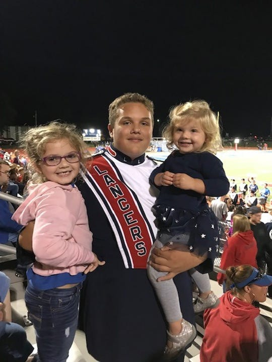 "Braden Poling poses for a photo in his band uniform alongside Haiden and Fiona Williams, who are described as his ""little sisters"" in his obituary."