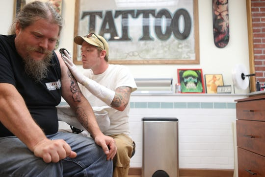 Co-owner and Chef at Fink's BBQ Smokehouse, Dave Finkelstein, reacts as he gets a tattoo at Hommage Tattoo Studio, by Kurt Stender. Tuesday, August 13, 2019