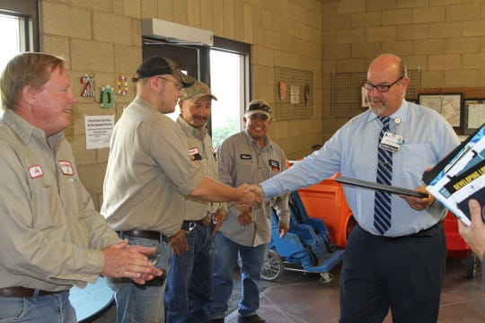 White Sands Beautification Committee Chair Christopher Hayman shakes the hands of staff, while Alameda Zoo Manager Johnny Crain stands on the far left, ready to shake his hand.