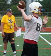 North Farmington High School varsity football player Jacob Bousimra takes a turn at QB during an Aug. 13 practice.
