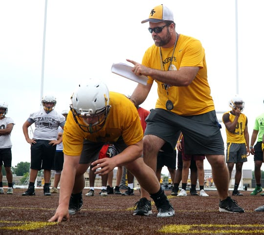 North Farmington varsity football head coach Jon Herstein works with his linemen in proper positioning during an Aug. 13 practice at the school.