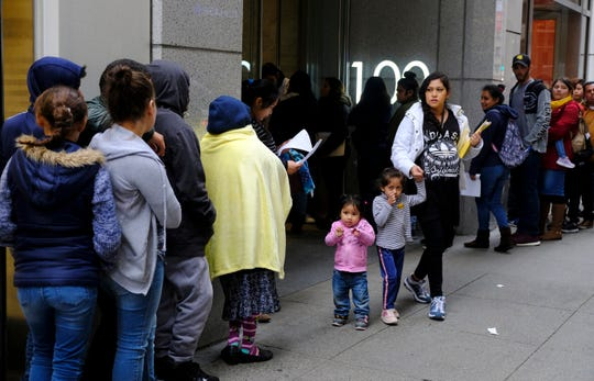 """In this Jan. 31, 2019, file photo, hundreds of people overflow onto the sidewalk in a line snaking around the block outside a U.S. immigration office with numerous courtrooms in San Francisco. Santa Clara and San Francisco have filed suit against the Trump administration over its new controversial """"public charge"""" rule that restricts legal immigration. This lawsuit is the first after the Department of Homeland Security's announcement Monday, Aug. 12, 2019, that it would deny green cards to migrants who use Medicaid, food stamps, housing vouchers or other forms of public assistance. (AP Photo/Eric Risberg, File)"""