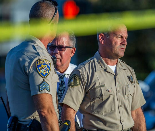 Riverside County Sheriff Chad Bianco, right, with Riverside City Police Chief Sergio G. Diaz, center, and a California Highway Patrol officer gather information after a shootout near a freeway killed a CHP officer and wounded two others before the gunman was fatally shot, Monday, Aug. 12, 2019, in Riverside, Calif.