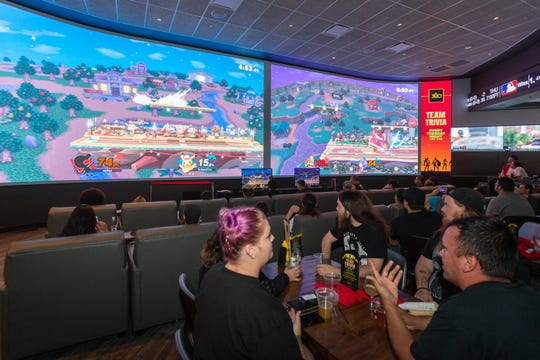 Esports gamers play video games on the big screens at the sports bar at Agua Caliente Casino.
