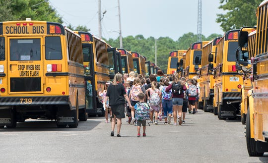 Students load Santa Rosa County School District after school at Holley-Navarre Middle School on Tuesday.