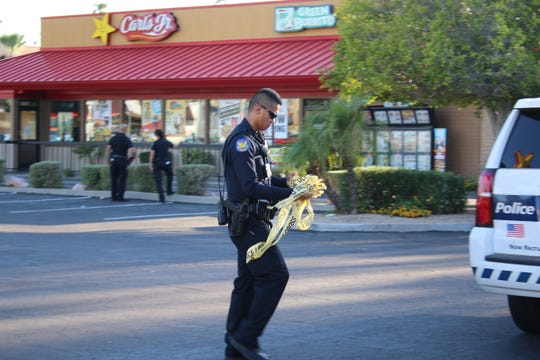 A police officer balls up police tape after the Carl's Jr. was determined safe for people to reenter. Police were responding to reports that a man with a gun was inside the restaurant.
