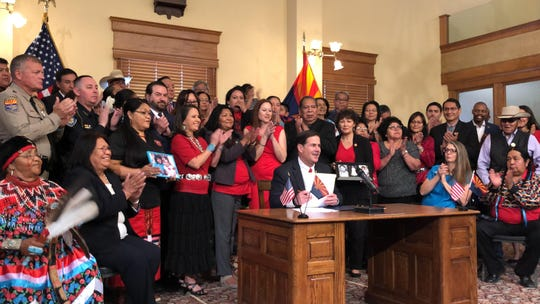 Gov. Doug Ducey smiles after signing of House Bill 2570, a law that creates a task force dedicated to studying the murders and disappearances of Indigenous women in Arizona.
