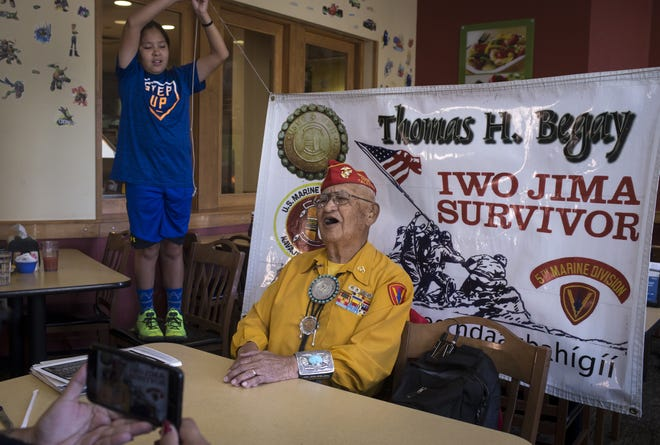 Navajo Code Talker Thomas H. Begay sings the Marines' Hymn on July 13, 2019, at Furr's Buffet Fresh in Albuquerque, New Mexico. Holding the banner is Begay's grandson Ronald Thomas H. Begay, 11.