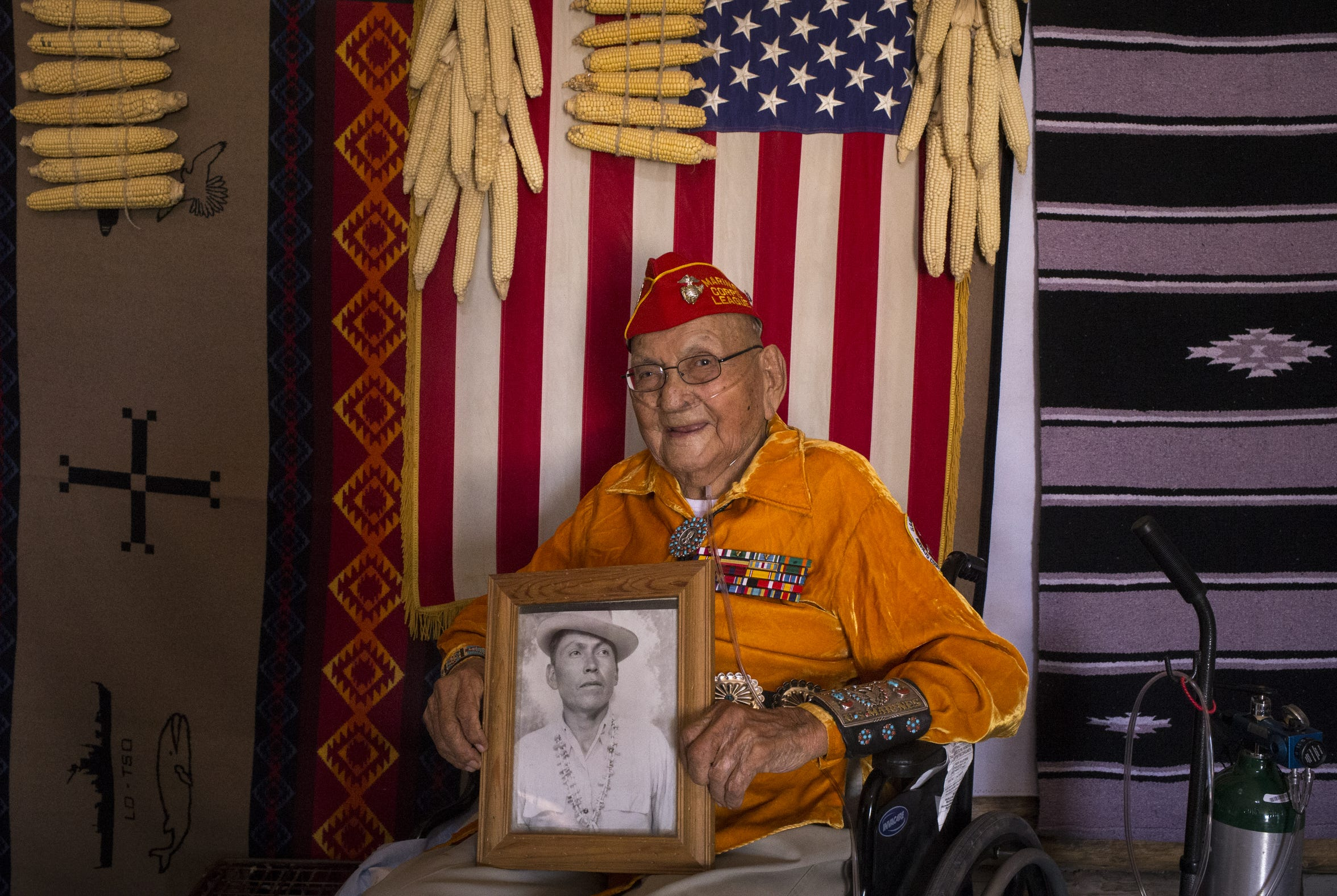 A portrait of Navajo Code Talker Joe Vandever Sr. holding an old photo of himself on July 10, 2019, in his family's hogan in Haystack, New Mexico.