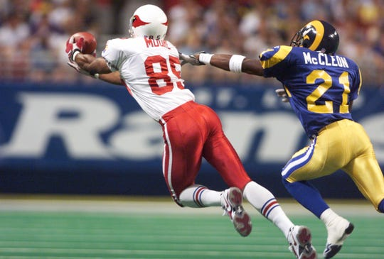 Cardinals receiver Rob Moore stretches out to make a catch in front of the Rams  safety Dexter McCleon on Sept. 27, 1998.
