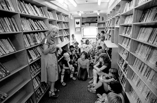Children listen to a librarian. Bookmobiles first appeared in Phoenix in the 1940s.