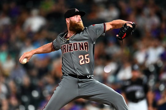 Diamondbacks reliever pitcher Archie Bradley (25) delivers a pitch during the ninth inning of a game against the Rockies on Aug. 12 at Coors Field.