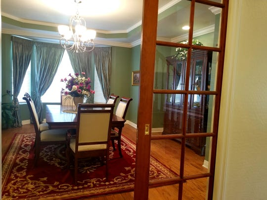 A Persian rug anchors the dining room table. Paned pocket doors add an eclectic feature to the office, parlor and dining rooms.