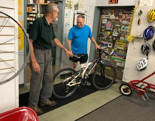 Pedallers Bike Shop owner Bob DeRoo, left, pauses to help a visitor who's having a problem with his bike.