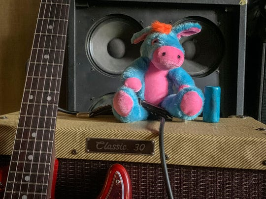 A colorful stuffed donkey sits on an amp while the Johnny Wheels and the Swamp Donkeys band practices August 6, 2019, in Sheridan, Oregon. The band will represent the Cascade Blues Association at the 2020 International Blues Challenge in Memphis. Kennicott sings and plays the harmonica, both challenging because he has a partially paralyzed diaphragm from a childhood swimming/diving accident that left him in a wheelchair.