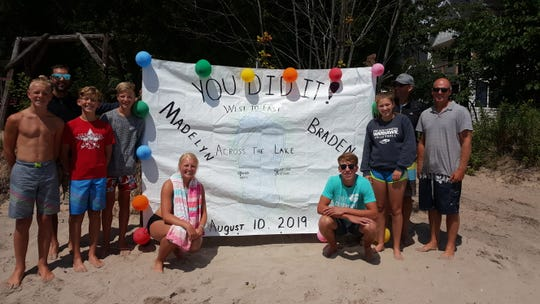 Madelyn Hendrikse (lower left) and Braden Dirkse (lower right) stand with family and friends after water skiing across Lake Michigan.