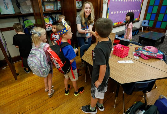 First grade teacher Kayla Watson collects supplies from students on the first day of school at Sunshine Elementary School on Tuesday, Aug. 13, 2019, in Springfield, Mo.