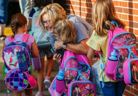 Tracy Daniels, the principal at Sunshine Elementary School, greets students as they arrive for the first day of school on Tuesday, Aug. 13, 2019, in Springfield, Mo.