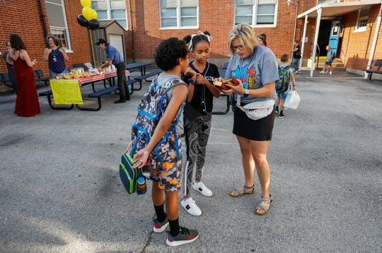 Tracy Daniels, principal at Sunshine Elementary, looks at a gift that McKenna Satterfield, 10, center, and Stella Satterfield, 8, gave her on the first day of school on Tuesday, Aug. 13, 2019, in Springfield, Mo.