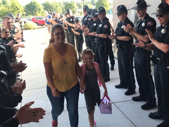 Kim Roberts and her daughter, Lydia, enter Fremont Elementary School in Springfield. They were flanked by deputies from the Greene County Sheriff's Office.