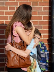 Sarah Allen hugs her son Grant Allen, 10, after dropping him and his brother Mason Allen, 8, off for the first day of school at Sunshine Elementary School on Tuesday, Aug. 13, 2019, in Springfield, Mo.