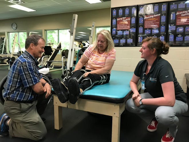 Licensed physical therapist Lee Baker and Meagan Pritchard, physical therapy student from Mary Baldwin's Murphy Deming College of Health Sciences, help Pat Ward learn how to use her braces during a neuro-wellness class at the Staunton-Augusta YMCA on Monday, Aug. 12, 2019. Ward suffered a spinal cord stroke and participates in the class to continue needed therapies no longer covered by healthcare insurance.